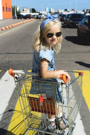 little adorable female child having fun in shopping cart at parking