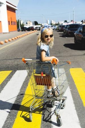 little adorable female child in sunglasses having fun in shopping cart on crosswalk