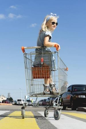 little stylish female child in sunglasses having fun in shopping cart at parking