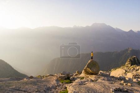 male tourist stand on rock against cliff and hills on background, Alpine region of Switzerland