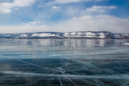 Photo for View of ice water surface under cloudy sky during daytime with hills on shore, russia, lake baikal - Royalty Free Image