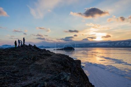 Photo pour Vue lac avec formations de surface et rochers de glace avec les gens debout sur le rivage sur soleil couchant, Russie, lac Baïkal - image libre de droit