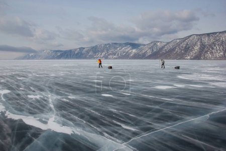 male hikers with backpacks walking on ice water surface during daytime,,russia, lake baikal