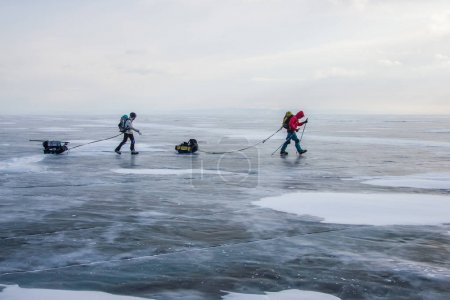 Photo for Male hikers with backpacks walking on ice water surface during daytime,,russia, lake baikal - Royalty Free Image