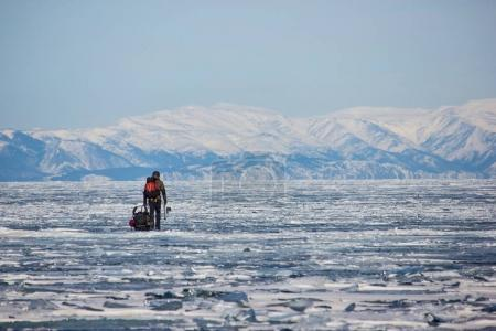 Photo pour Randonneur masculin avec sac à dos debout sur la surface de l'eau glacée, la Russie, lac baikal - image libre de droit
