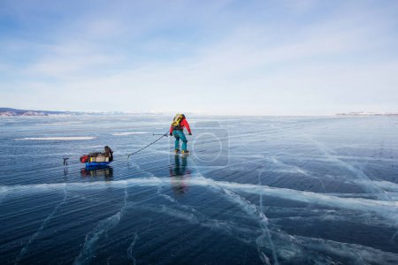 male hiker with backpack walking on ice water surface,russia, lake baikal