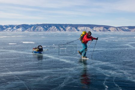 male hiker with backpack walking on ice water surface,,russia, lake baikal