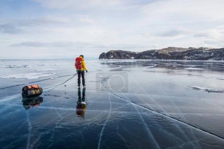 man with backpack going through ice water surface and hills on background, Russia, Lake Baikal