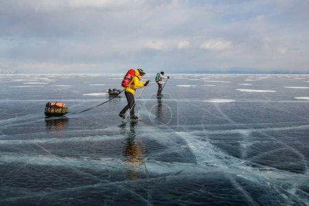 dos hombres con mochilas pasando por la superficie del agua helada y colinas en el fondo, Rusia, el lago Baikal