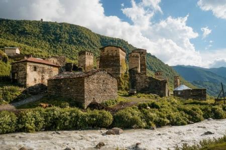 Photo for Old weathered buildings against small river stream against hills, Ushguli, svaneti, georgia - Royalty Free Image