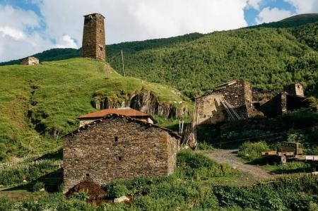 Photo for View of grassy field with old weathered rural buildings and hills on background, Ushguli, svaneti, georgia - Royalty Free Image