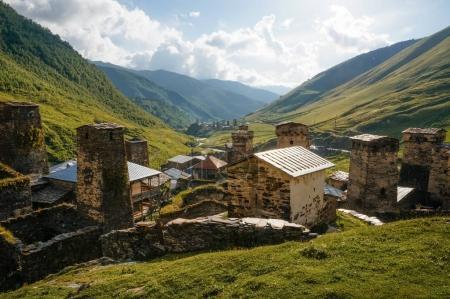 Photo pour Vue du champ herbeux avec de vieux bâtiments ruraux altérés et des collines sur le fond, Ushguli, svaneti, géorgie - image libre de droit