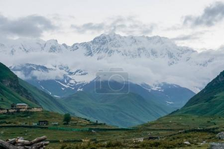 view of green grass meadow with houses and buildings and mountains on  background, Ushguli, svaneti, georgia