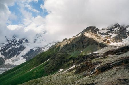 view of snowy mountain peaks with grass on slopes under clouds, Ushguli, svaneti, georgia