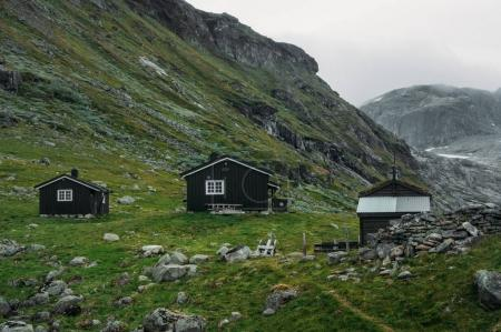 Photo for View of field with green grass and scattered stones against small rural houses, Norway, Hardangervidda National Park - Royalty Free Image