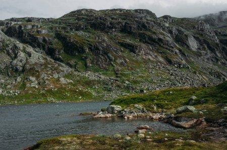 Photo pour Vue sur la rivière de montagne, entourée de collines et de pierres sur la rive, la Norvège, le Parc National de Hardangervidda - image libre de droit