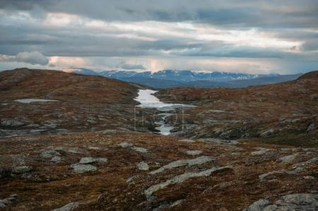 field with small water ponds and mountains on background during stormy weather, Norway, Hardangervidda National Park