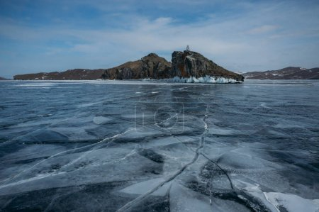 View of ice covered water surface of lake and rock formations on background, Russia, Lake Baikal