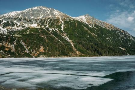 Photo pour Vue sur la montagne enneigée et le lac avec glace, Morskie Oko, Sea Eye, Parc national des Tatra, Pologne - image libre de droit