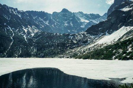 Photo pour Vue sur les sommets rocheux avec lac à pied avec de la glace sur la surface de l'eau, Morskie Oko, oeil de la mer, Parc National des Tatras, Pologne - image libre de droit