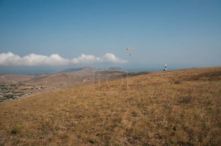 Parachute in the sky over field in hillside area of Crimea, Ukraine, May 2013