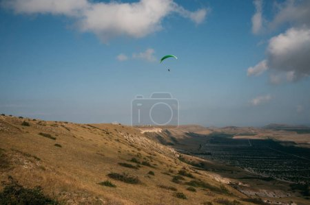 Parachutist gliding in blue sky over scenic landscape of Crimea, Ukraine, May 2013