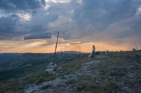 Woman walking in beautiful mountainous landscape with windsock waving in Crimea, Ukraine, May 2013