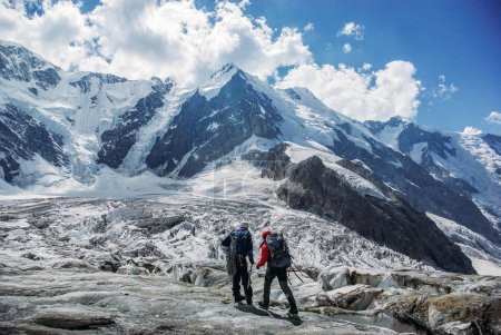 Photo for Male travelers hiking in snowy mountains, Russian Federation, Caucasus, July 2012 - Royalty Free Image