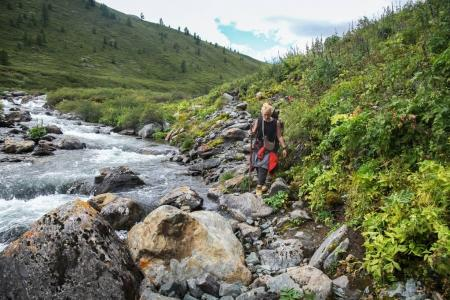young backpacker walking near river in Altai, Russia