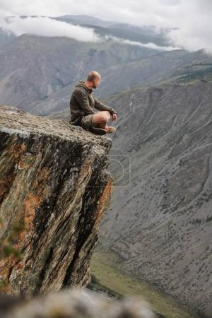 Photo for Young man sitting on cliff and looking beautiful landscape, Altai, Russia - Royalty Free Image