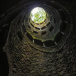 Bottom view of light and trees in the end of spira...