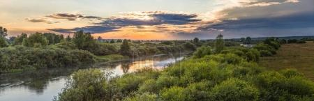 scenic landscape with calm river and green vegetation at sunrise, neman, belarus