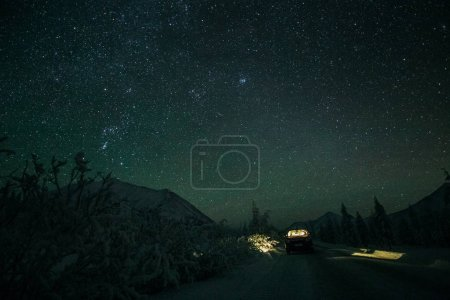 Photo for Car standing on winter road and beautiful starry sky in mountains at night, Yakutia - Royalty Free Image