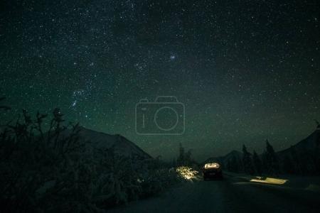 Photo pour Voiture debout sur la route d'hiver et beau ciel étoilé dans les montagnes la nuit, Yakutia - image libre de droit