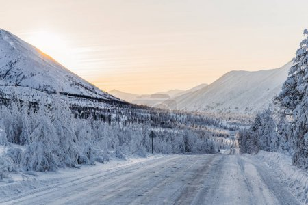 Photo for Beautiful snow covered winter road with road sign and trees in mountains, kolyma highway - Royalty Free Image