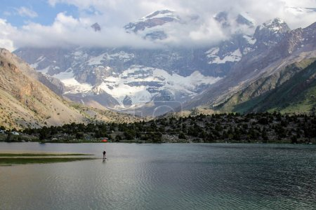 Photo pour Homme seul debout sur le lac et le beau paysage de neige scénique incroyable plafonné lac kulikalon montagnes, Tadjikistan, - image libre de droit