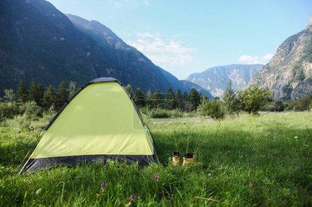 Photo pour Tente avec des chaussures sur l'herbe verte dans de belles montagnes, Altaï, Russie - image libre de droit