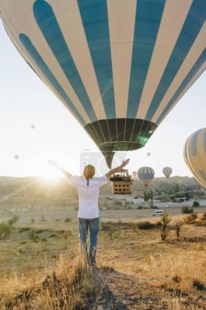 Photo for Back view of man and hot air balloon flying in Goreme national park, fairy chimneys, Cappadocia, Turkey - Royalty Free Image