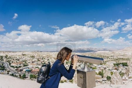 female tourist looking at city through binocular viewer, Cappadocia, Turkey
