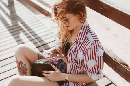 attractive young woman sitting on floor of wooden pier and using smartphone