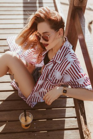 high angle view of young woman sitting on wooden pier with plastic cup of cocktail