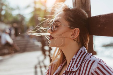 close-up portrait of beautiful young woman sitting on wooden pier
