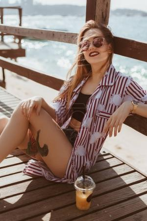 attractive young woman sitting on floor of pier at beach