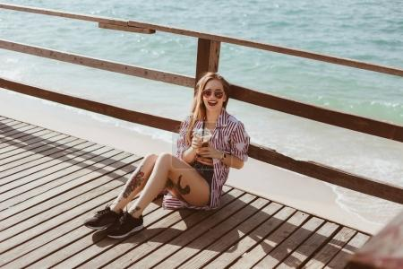 laughing young woman with plastic cup sitting on wooden pier in front of sea