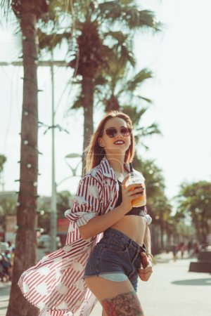 happy young woman drinking mango shake on sunny street with palm trees