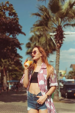 Photo for Smiling young woman drinking mango shake on sunny street with palm trees - Royalty Free Image