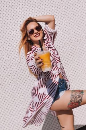 beautiful young woman with plastic cup of cocktail leaning back on white wall