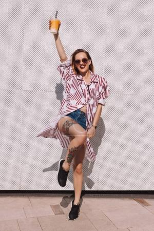happy woman holding plastic cup of cocktail in front of white wall