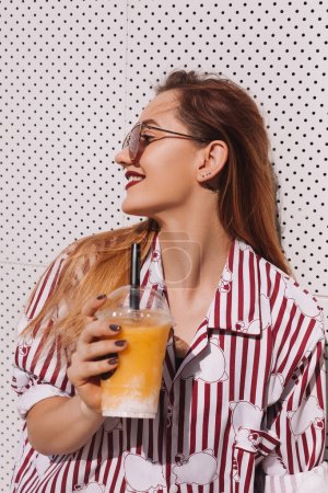 Photo for Sensual woman with plastic cup of refreshing cocktail leaning back on white wall - Royalty Free Image