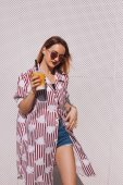 beautiful young woman in striped red shirt with mango shake in plastic cup